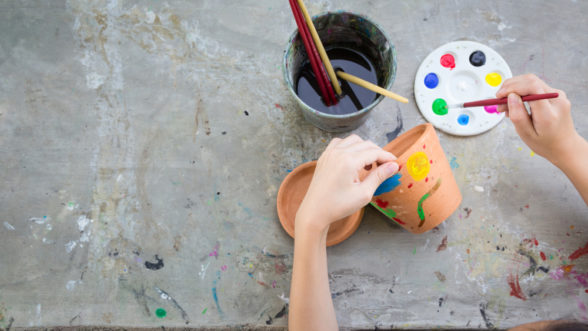 Child painting clay pot during a fun pottery project