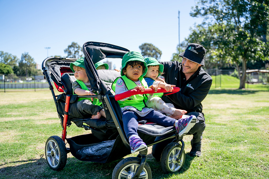 Four children in quad pram with educator at the park