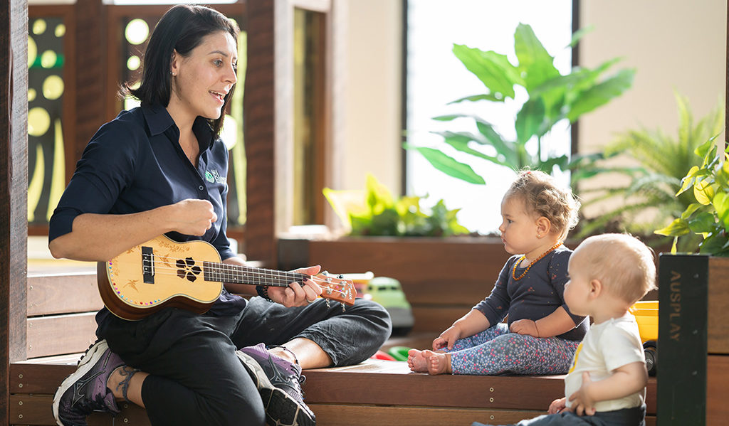 Teacher playing instrument to two children