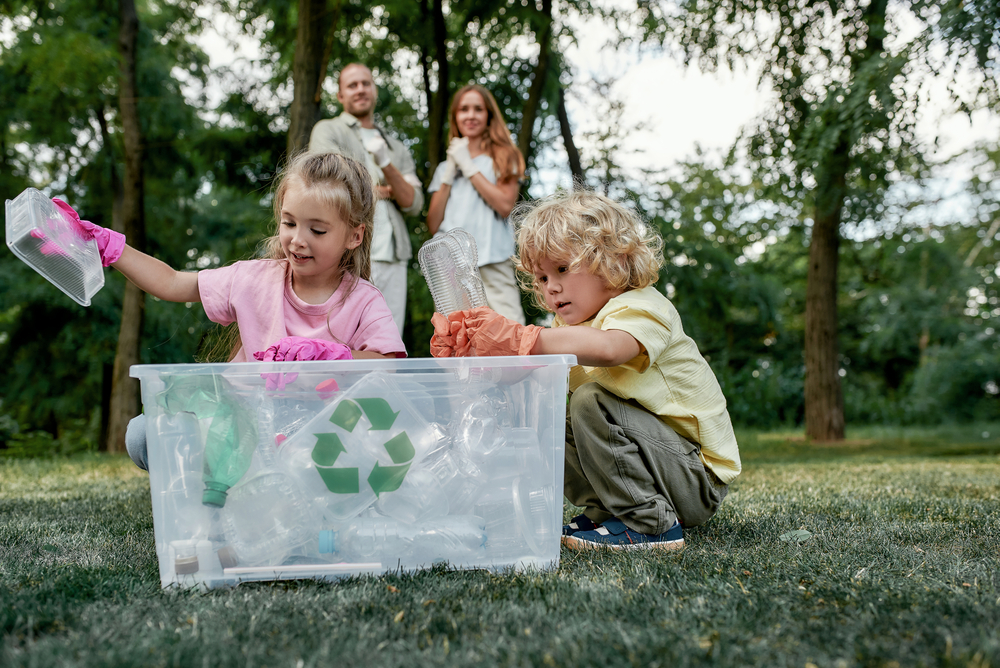 Two children putting recycling into the recycling bin