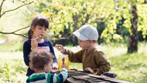 three children eating honey at a park