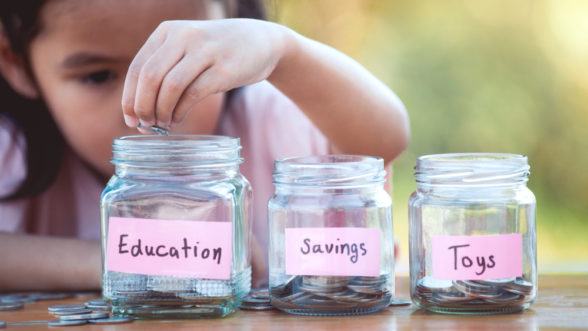 girl putting money into savings jars
