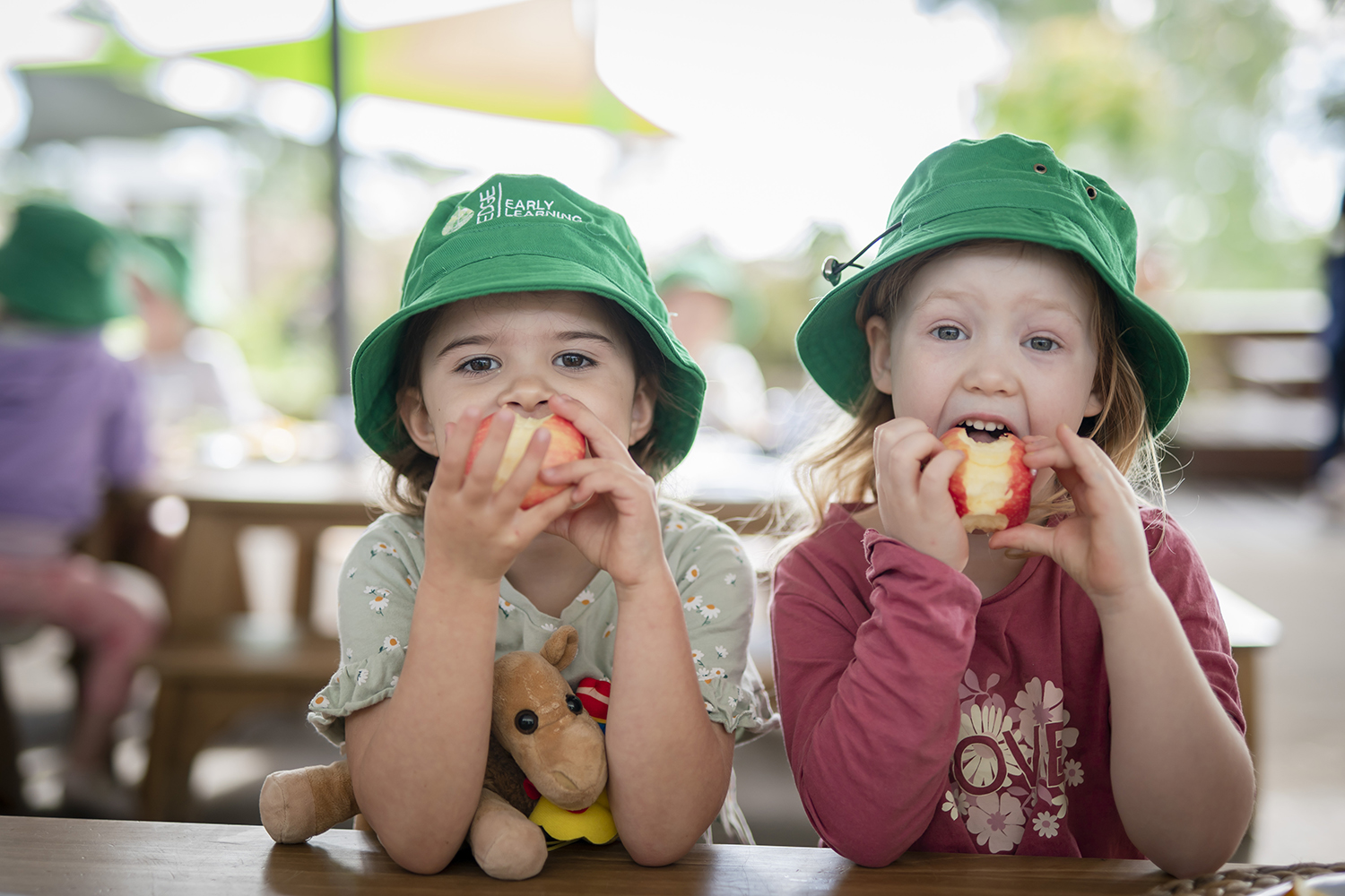 Two girls eating apples