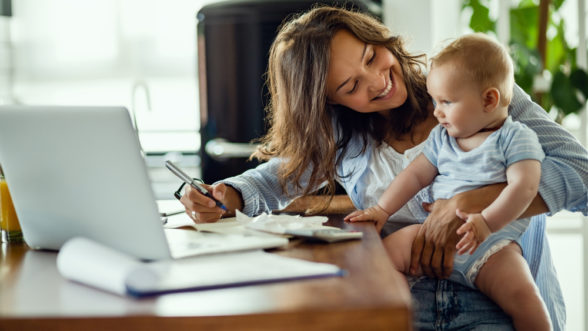 Mother holding baby doing paperwork