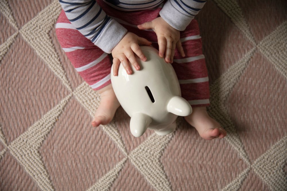 Baby holding piggybank