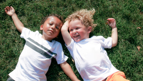 Two little boys laying on the grass